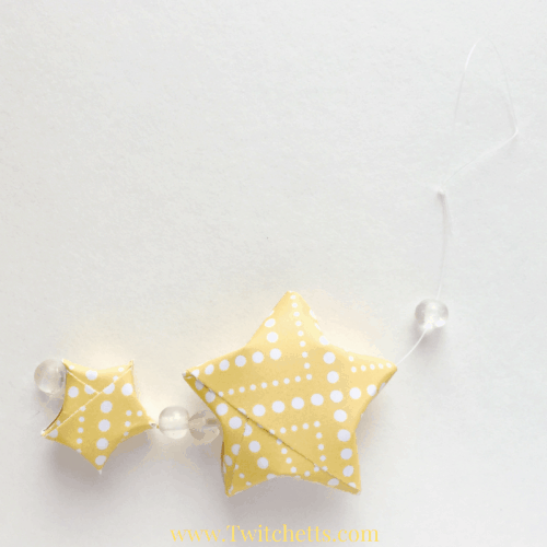 Learn how to fold these adorable paper stars! They are perfect for all sorts of decoration ideas, but these paper star ornaments are the cutest!