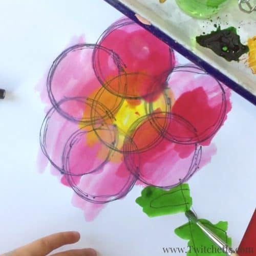 Create fidget spinner art by putting a pen in the hole and drawing circles. Add watercolors to make them vibrant and fun.