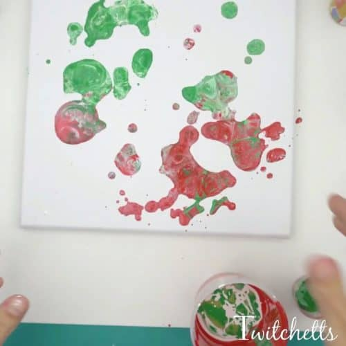 Create these beautiful poured Christmas rocks using acrylic paint and an inexpensive thickening agent. Pour painting is a fun process art technique that will mesmerize your kids.