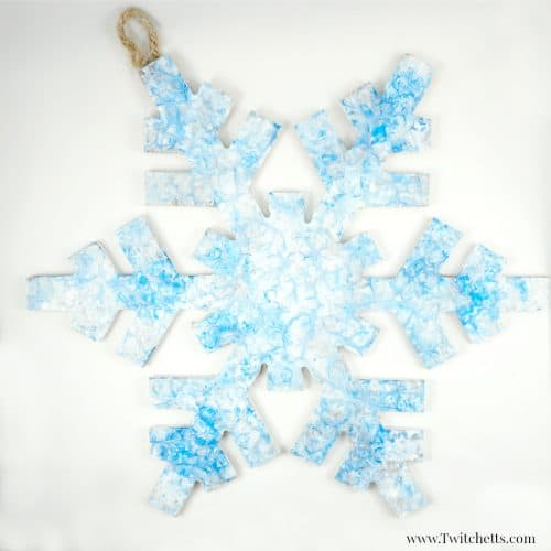 Create press painting snowflake decorations. This creative painting technique is a fun way enjoy painting with kids.