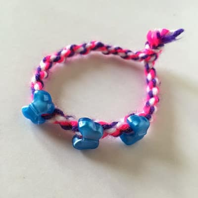 Make these Quick and Easy 2 Minute Twisted Bracelets for your kiddos. A perfect first bracelet design. Easy to put on and take off for toddler bracelets.