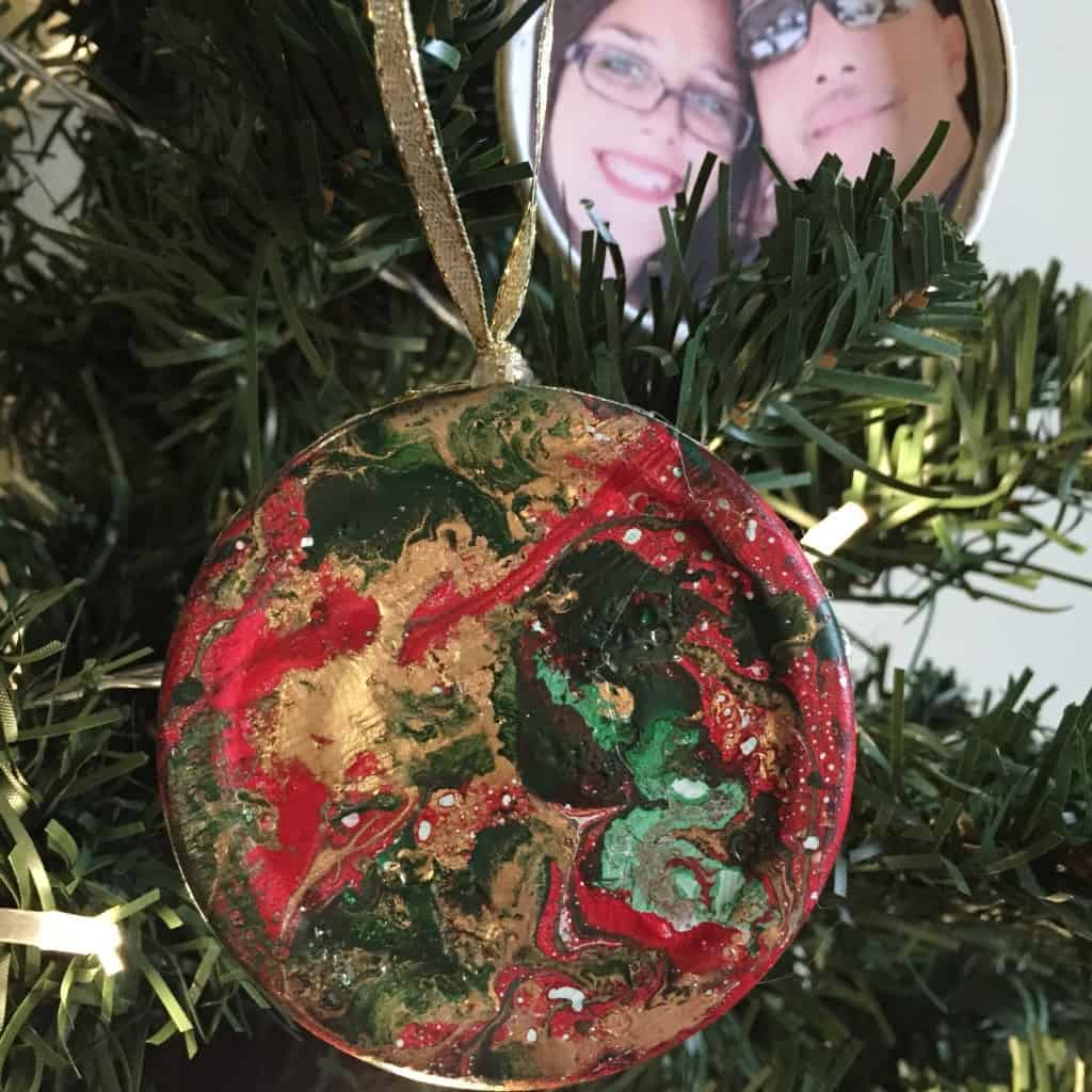 Create these DIY Marbled Picture Christmas Ornaments using upcycled jar lids. This craft is fun and easy to create for beautiful photo holding decoration.