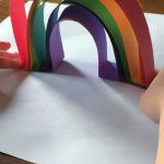 Image of child making a paper rainbow.