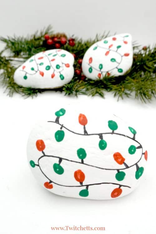 This Christmas lights rock art is easy, fun, and a perfect painted rock to give as a gift or hide in your nearest park. #christmas #rocks #christmaslights #rockpainting #stonepainting #rockpaintingideasforkids #stockingstuffer #christmasartproject #fingerprint #twitchetts