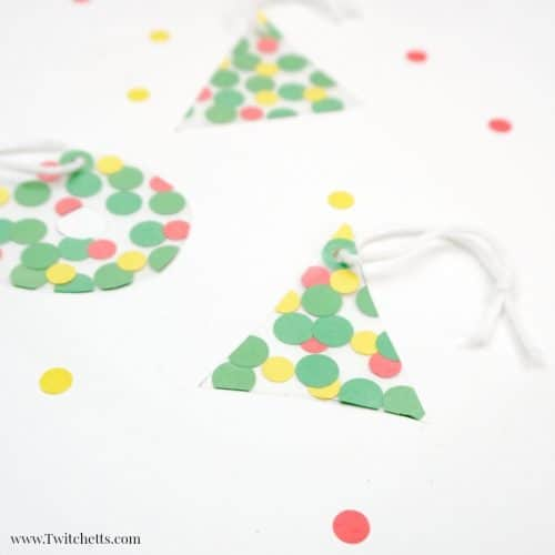 This fun fine motor Christmas ornament uses inexpens-ve construction paper to create a suncatcher that can be given as a gift or hung on your tree. #finemotor #christmasornaments #suncatcher #nomess #easyornaments #preschool #toddler #classroom #twitchetts