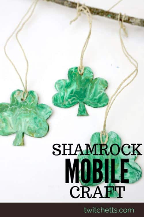 Create a beautiful pour painted shamrock mobile. This one of a kind St Patrick's Day art project will make a fun decoration for your classroom or playroom! #twitchetts