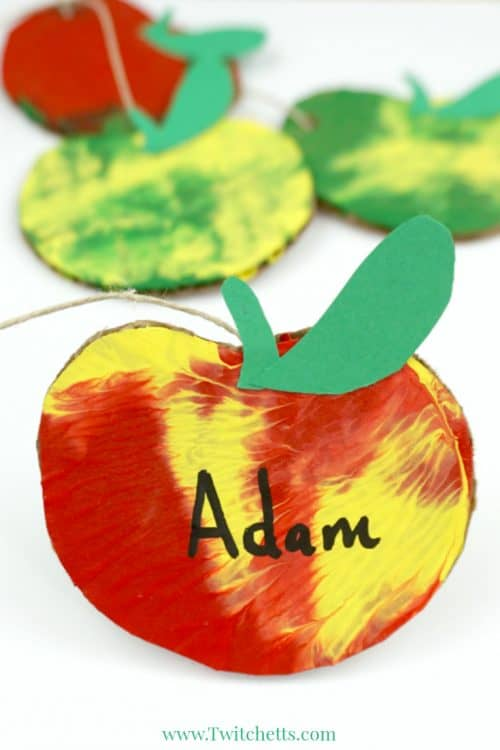 This apple themed press painted garland is so much fun to make! Apples are the perfect way to decorate a classroom for back to school or your living room for fall. Plus your kids will love that can help make them! #apple #fall #autumn #backtoschool #classroomdecor #garland #mobile #presspainting #creativepainting #twitchetts
