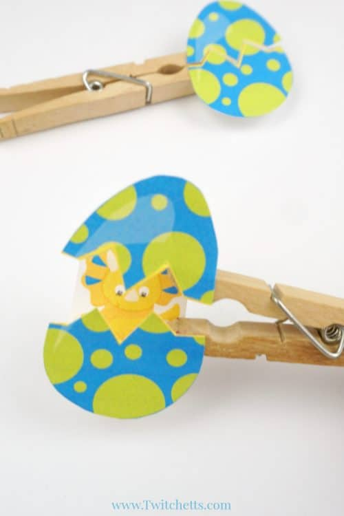 This hatching dinosaur egg craft  is lots of fun and a great craft for preschoolers. Grab our template and a couple of simple craft supplies and you have a fun craft that your child will want to play with! #hatchingdinosaureggcraft #dinosaur #egg #hatching #craftforkids #clothespin #template #twitchetts