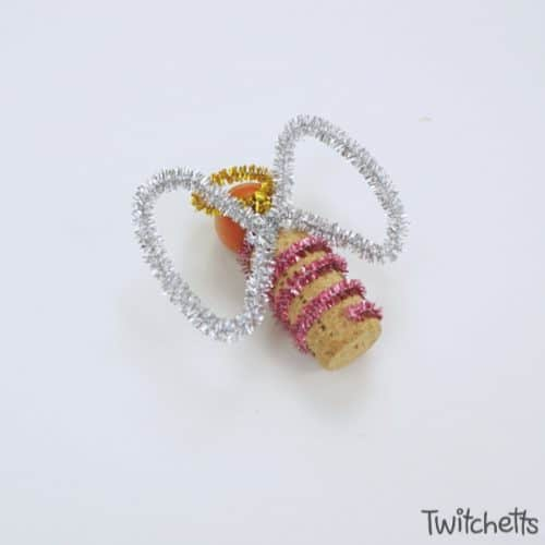 Make these fun angel wine cork Christmas ornaments to give as gifts or to hang on your tree. Kids will love creating these singing angels. #angel #christmasornament #winecork #bead #angeldecorations #giftidea #ornamentskidscanmake #craftsforkids #twitchetts