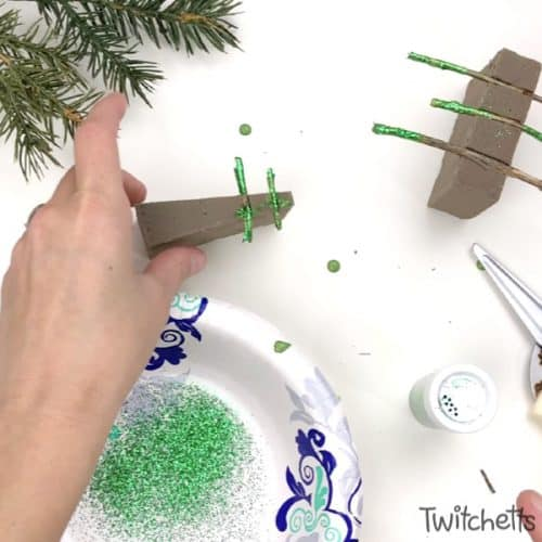 Make sparkly tree-shaped Christmas ornaments using sticks you have laying in your yard. Simple supplies and a Christmas decoration that shimmers. Your kids will be so proud to give these ornaments as gifts.  #nature #christmastree #christmasornament #sparkly #kids #twitchetts
