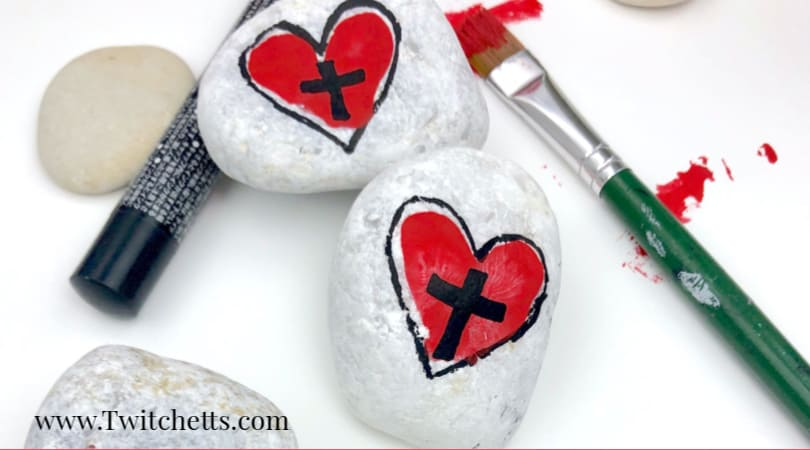 Create easy and fun heart and cross rocks with this simple tutorial. Use fingerprints to create this cross rock painting idea! #twitchetts
