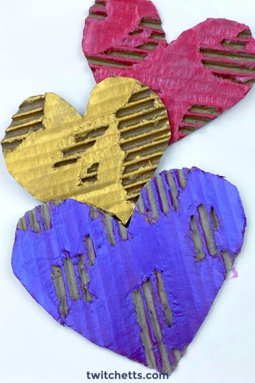 Completed painted cardboard heart decorations.