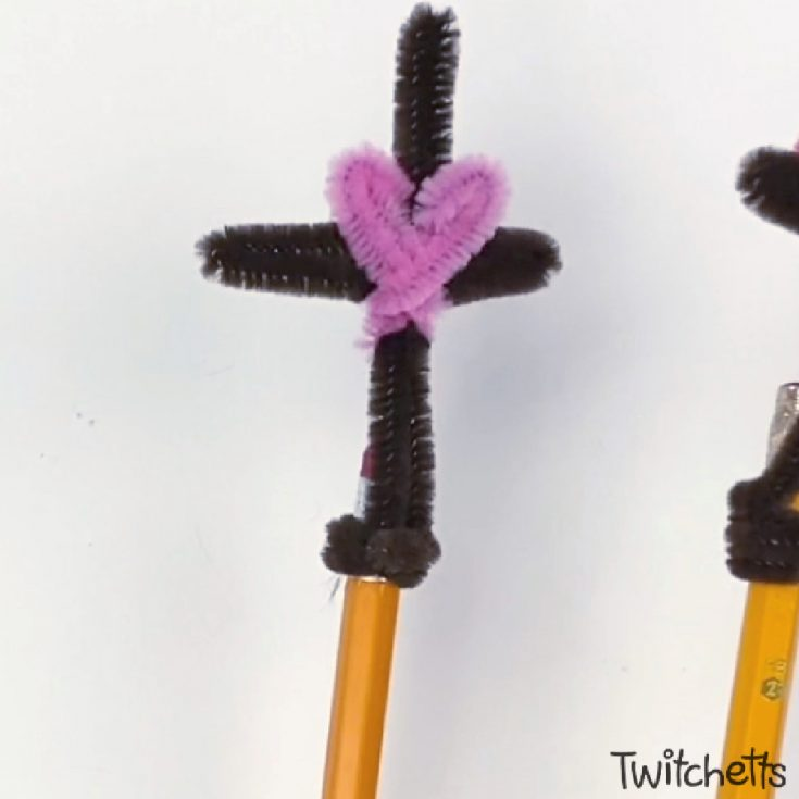 Image of a cross pencil topper made with pipe cleaners.
